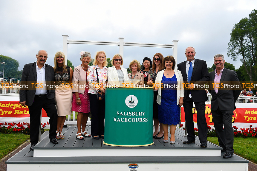Connections of Exceeding Power receive their trophy after winning The Total Decor Ltd Handicap during Ladies Evening Racing at Salisbury Racecourse on 15th July 2017