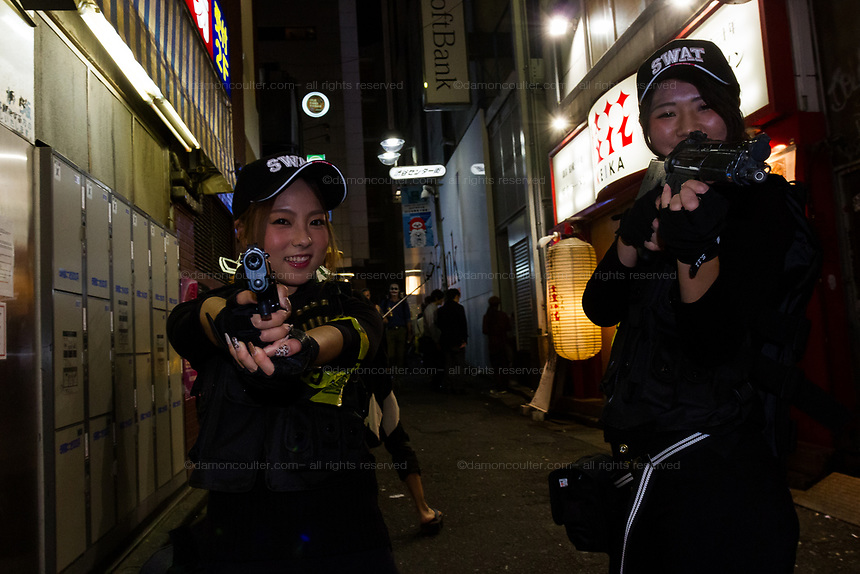 Two Japanese women dressed as a SWAT team during the Halloween celebrations Shibuya, Tokyo, Japan. Saturday October 27th 2018. The celebrations marking this event have grown in popularity in Japan recently. Enjoyed mostly by young adults who like to dress up, drink , dance and misbehave in parts of Tokyo like Shibuya and Roppongi. There has been a push back from Japanese society and the police to try to limit the bad behaviour.