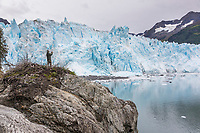 Man views the tidewater face of Meares glacier in Prince William Sound, Alaska.
