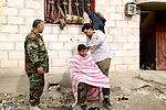 27/2/2015--Kobane,Syria-- Shallaw is a doctor who came to Kobane from south Kurdistan to help peshmarga and treat them when they are injured and some time he is cutting Peshmerga's hair.