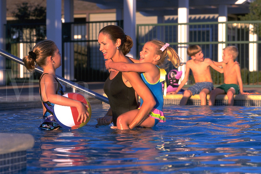 mother playing with her 4 children in a swimming pool in an upscale residential swimming pool in the development's clubhouse swimming pool. mother and children in swimming pool. swimming pool.