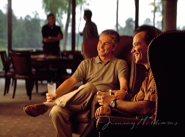 Two men enjoy drinks together inside of a luxurious Country Club