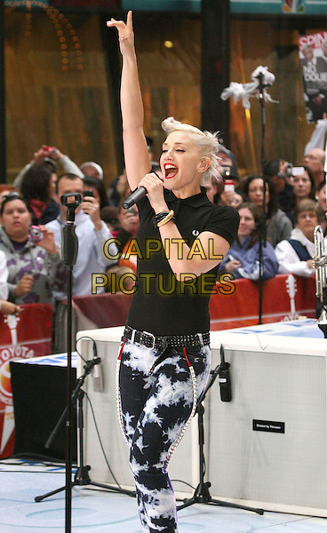 GWEN STEFANI - NO DOUBT .No Doubt performs on NBC's Today Show Concert at Rockefeller Center, New York, NY, USA, .1st May 2009..half length gig live on stage show concert performing microphone black Fred Perry polo t-shirt buttons collar  bracelet studded belt hair twisted buns knots pinned up red lipstick braces tie dye bleached denim jeans singing hand arm raised up .CAP/ADM/AC.©Alex Cole/AdMedia/Capital Pictures