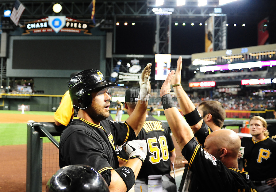 Apr. 17, 2012; Phoenix, AZ, USA; Pittsburgh Pirates first baseman Garrett Jones is congratulated by teammates after hitting a solo home run in the sixth inning against the Arizona Diamondbacks at Chase Field. The Pirates defeated the Diamondbacks 5-4. Mandatory Credit: Mark J. Rebilas-