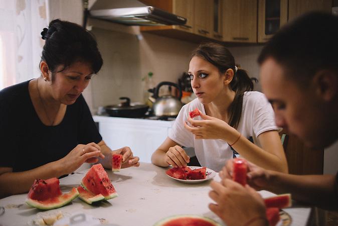 Alexander, Katrine and her mother eat watermelon at kitchen. Ribnita, Transnistria