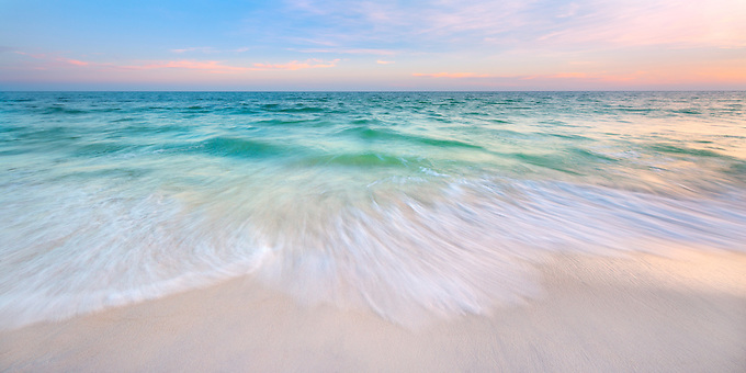 A soft pastel sky at sunset reflected on the emerald green waters of Florida's Gulf Coast.