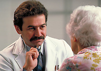 Doctor listening to elderly, senior, female patient, warm, smiling expression, communication, occupations, medical, health care.