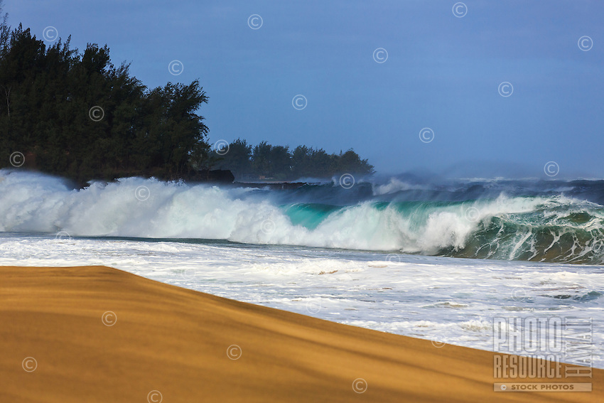 A long and powerful wave breaks over a frothy line of white and turquoise blue water at Lumaha'i Beach, northern Kaua'i.