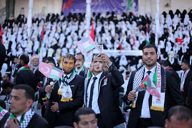 Palestinian grooms take part in a mass wedding ceremony in Gaza City, on May 31, 2015. Nearly 2000 Palestinian couples were married in a ceremony funded by the Turkish government and supported by the Hamas movement. Photo by Ashraf Amra