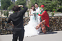 Paris, France. 09.05.2015. A bride and a groom's photographs are crashed by a clown on a bridge over the Seine. Photograph © Jane Hobson.
