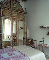 A massive antique inlaid wardrobe takes up an entire wall of this bedroom