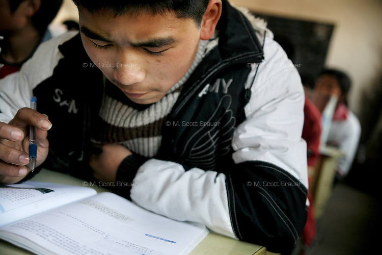 A schoolboy studies during class at Yixing Middle School in Lianshui County, Jiangsu Province, China.  The Pfrang Association, a German charity based in Nanjing, China, sponsors a number of children in the school, providing money for boarding, food, clothing, school supplies, and other necessities to continue schooling.  The majority of children at this school come from poor farming families in rural Jiangsu Province, China.