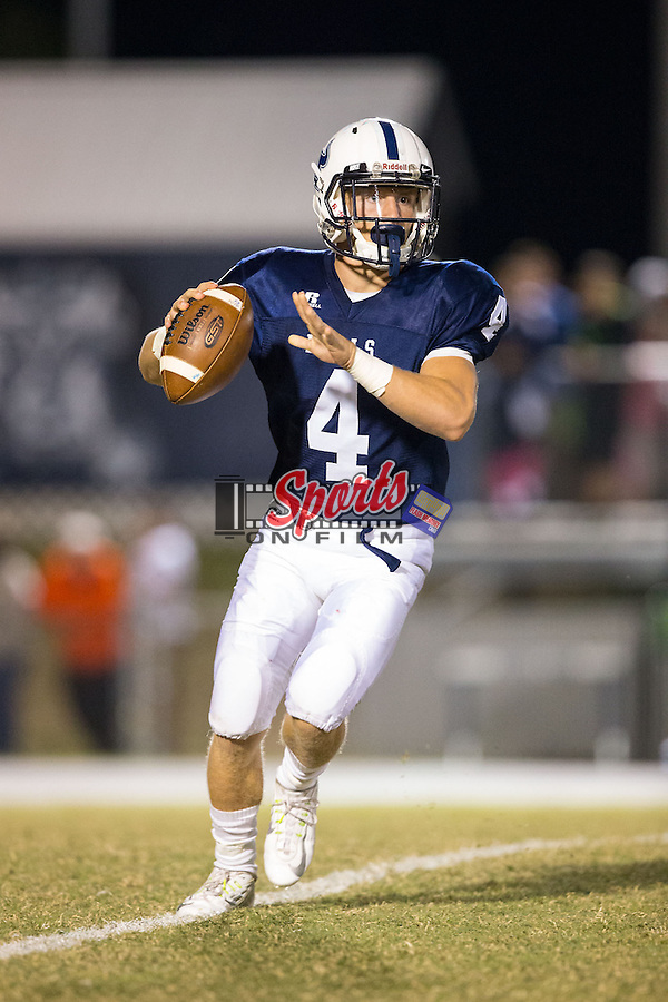 Nate Mullen (4) of the Hickory Ridge Ragin' Bulls rolls to his right looking to pass the ball during first half action against the Northwest Cabarrus Trojans at Hickory Ridge High School on October 17, 2014 in Harrisburg, North Carolina.  The Ragin' Bulls defeated the Trojans 34-6.  (Brian Westerholt/Sports On Film)