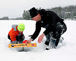 A boy and his dad reel in a fish on a frozen lake in the Northwoods.