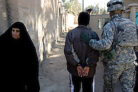 A US soldier from second platoon, Alfa company, 1st battalion, 506th, 101st airborne division escorts a suspected sunni insurgent to a vehicle that will take him to a US detention center to be interrogated while executing OPERATION TEEN WOLF, a raid in a neighborhood of western Ramadi with the purpose of searching for insurgency weapons, gather intel and meet with the civilian population, in the city of Ramadi, Iraq on Tuesday January 03 2006. during the raid four suspected Sunni insurgents were held  by the US military for further interrogations.