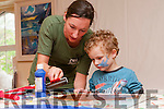 Meitheal Eitseala artist Deirdre McKenna helping little Liam O'Connor during the Féile na Bealtaine pop-up print studio in An Díseart over the weekend.