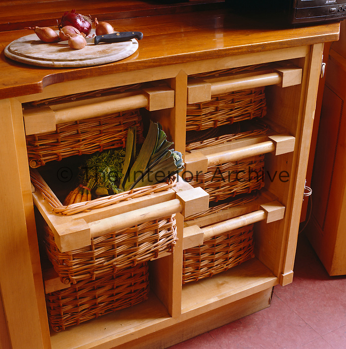 Detail of a kitchen storage unit with a series of six basket drawers for vegetables and fruit beneath a wooden work surface