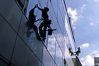 Window cleaners using abseil ropes on an office building in Akihabara, Tokyo, Japan. March 2006