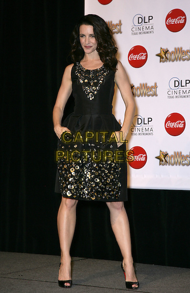KRISTIN DAVIS .SHOWEST Final Night Talent Awards at the Paris Resort Hotel and Casino,  Las Vegas, Nevada , USA,.18th March 2010..full length black dress gold metal studs embellished rivets hands in pockets sleeveless peep toe Christian Louboutin shoes .CAP/ADM/MJT.© MJT/AdMedia/Capital Pictures.