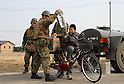 March 30, 2011, Ishinomaki, Miyagi, Japan - More than two weeks after the tsunami, volunteer groups look to contribute to the relief effort. An elementary school student tries to pedal his bike while it is loaded with water bottles. Members of the JSDF assist him. Many neighborhoods still have no water. (Photo by Wesley Cheek/AFLO) [3682].