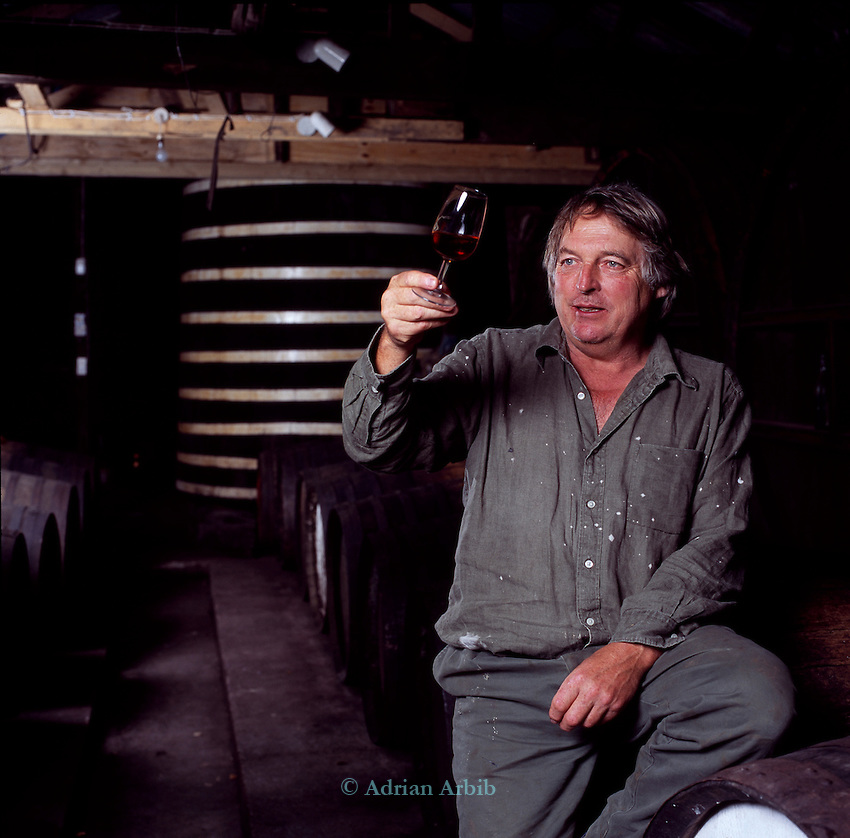 Julian Temperley of the Cider Brandy Company in Kingsbury Episcopi in his barrel room holding a  glass of Cider brandy to the light to check for clarity. .Julian uses Kingston Black apples for most of his cider production but mixes in other varieties for flavour.