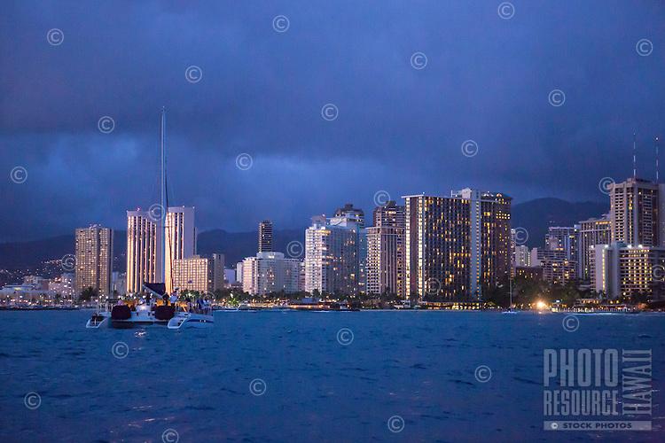 Catamaran off Waikiki at twilight in Honolulu, Oahu
