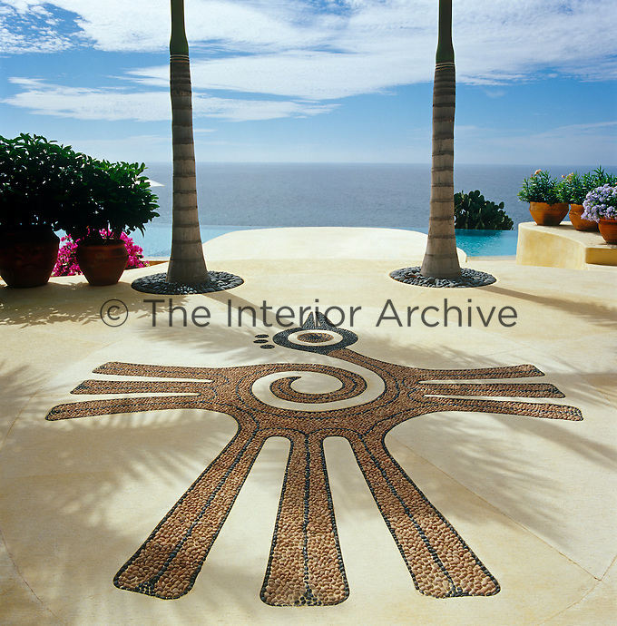 A bird of paradise motif, a replica of an Aztec symbol, is set into the concrete floor of the terrace