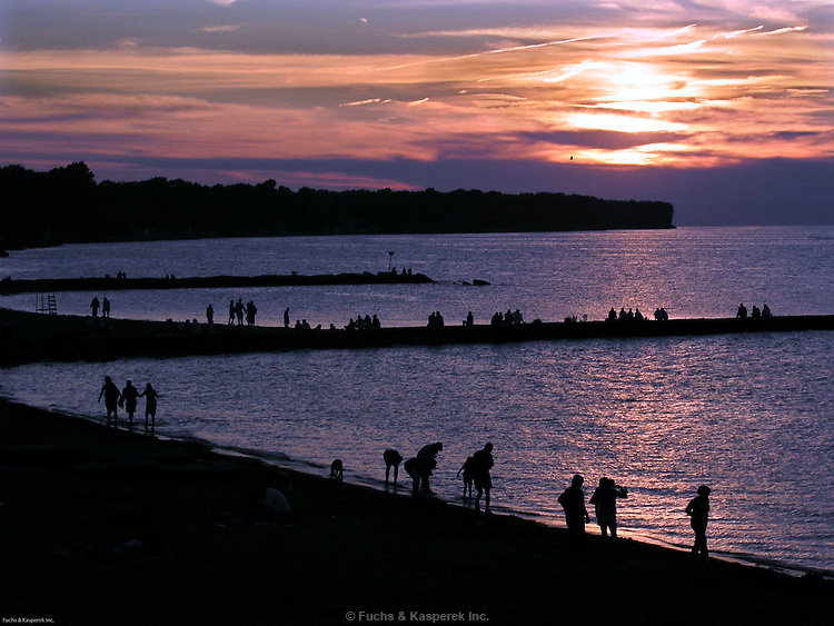 The beach and breakwalls are crowded with people to watch the summer sunset at the beach at the Huntington Reservation of the Cleveland MetroParks.