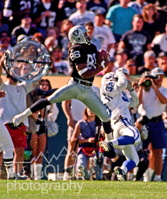 Oakland Raiders vs. Indianapolis Colts at Oakland Alameda County Coliseum Sunday, October  22, 1995.  Raiders beat Colts  30-17.  Oakland Raiders wide receiver Rocket Ismail (86) catches pass by out jumping Indianapolis Colts defensive back Eugene Daniel (38).