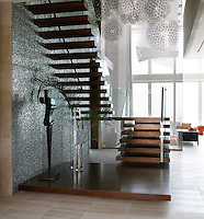 In the inspiring entrance hall, the stairway appears as a sculpture built onto a platform and a wall. Homage to Nijinski by Sorel Etrog stands tall next to an aluminum foam-panelled wall that shimmers beneath Moooi's perfect spheres punctuated by tiny LED lights.