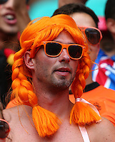 A Netherlands supporter wearing a bright orange wig