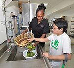 4-H ambassador Caleb Kinzinger, 16, from Freeburg, Ill and Jackie Joyner Kersee wash fresh-picked vegetables for a salad inside the JJK Center on Thursday, May 30, 2019 in East St. Louis, Ill. (Tim Vizer/AP Images for National 4-H Council)