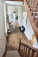 A spacious staircase hall with wide wood floorboards and a high ceiling