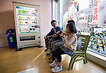 A family enjoys a break while sitting on a bench  next to a vending machine, both of which are made from recycled green tea leaves in Tokyo, Japan. The machine is manufactured by tea-maker ITO EN, LTD., which estimates that it generates approximately 40,000 tons of used tea leaves during the course of beverage manufacturing operations each year. ITO EN has developed a wide array of methods for recycling used tea leaves and incorporating recycled tea leaves into a range of products and materials, including pens, park benches and vending machines.