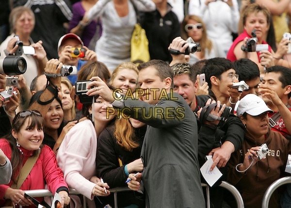 MATT DAMON.At The Warner Brothers' Hand & Foot Print Ceremony for Ocean's Thirteen at The Grauman's Chinese Theatre in Hollywood, California, USA..June 5th, 2006.half length grey gray suit fans audience camera taking picture photograph .CAP/DVS.©Debbie VanStory/Capital Pictures
