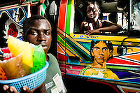 A Haitian street vendor passes the tap-tap bus on the street of Port-au-Prince, Haiti, 25 July 2008. Tap-tap vehicles serve as public transportation in Haiti. They are private, operate over fixed routes, departing only when full. Tap-taps are decorated with bright and shiny colors and with a lot of fancy designed elements. There are scenes from the Bible, Christian slogans, TV stars or famous football players often painted on a tap-tap body. Tap-tap name comes from sound of taps on the metal bus body signifying a passenger's request to be dropped off.