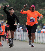 Brooksie-2.09292013<br /> Margie Lavelanet (right), Troy, celebrates with her &quot;BFF&quot; and running coach Coreen McCaul, Farmington Hills, after crossing the finish line in the rain during the Brooksie Way Half Marathon Sunday, Sept. 29, 2013. (Special to The Oakland Press / LARRY McKEE)