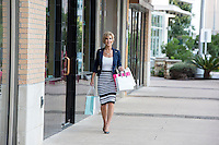 Elegant female mall shopper holds shopping bags and walks down the sidewalk at an Austin outdoor shopping center
