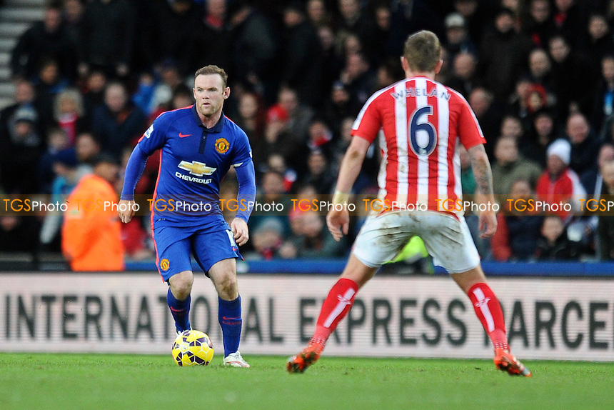 Wayne Rooney of Manchester United controls the ball in front of Glenn Whelan of Stoke City - Stoke City vs Manchester United - Barclays Premier League Football at the Britannia Stadium, Stoke-on-Trent - 01/01/15 - MANDATORY CREDIT: Greig Bertram/TGSPHOTO - Self billing applies where appropriate - contact@tgsphoto.co.uk - NO UNPAID USE