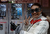 "A lay shows off her ""2018"" glasses in Ameyoko Market in Ueno district of Tokyo, Japan on New Year's Eve.   Picture by Richard Jones"