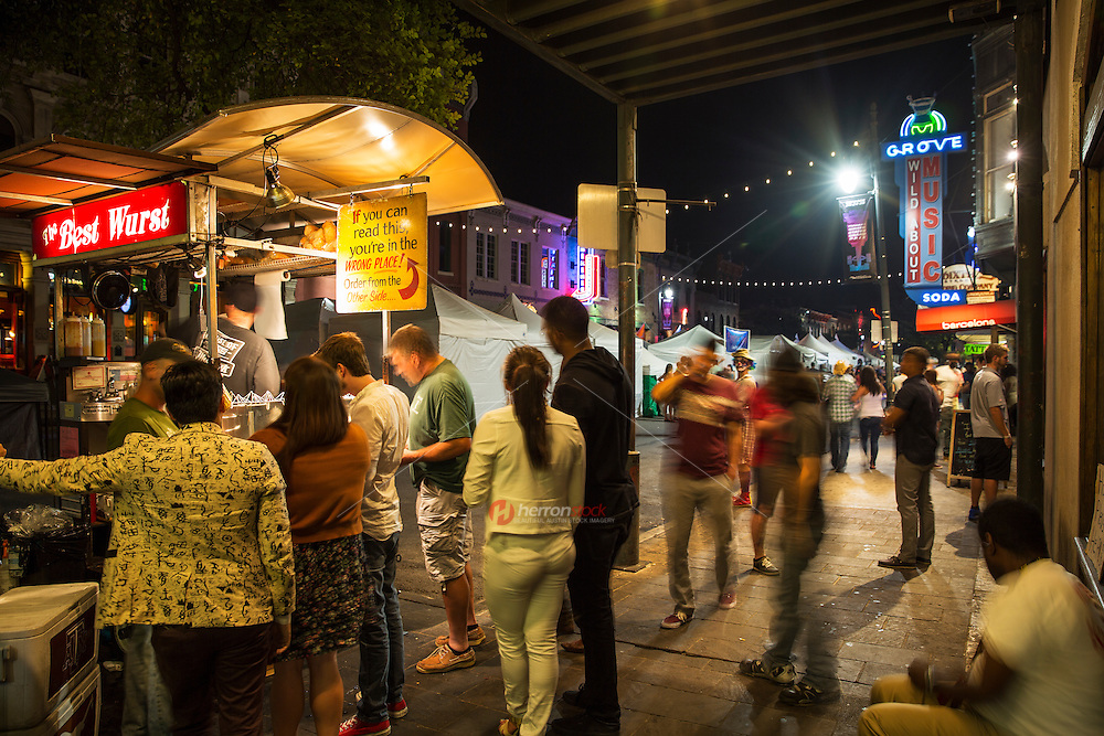 In this image, hungry sixth street locals and tourists stop and line up at one of the many food cart vendors that line the popular entertainment and bar district in downtown Austin, Texas - Stock Image.