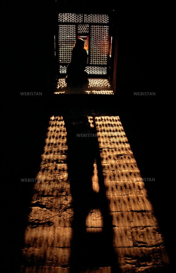 &Eacute;gypte, le Caire, 1991. Architecture &eacute;gyptienne traditionnelle. Une femme devant un Moucharabieh. Dans l'architecture arabe, ce balcon en bois, ferm&eacute; de grillage, forme l'avant-corps d'une fen&ecirc;tre et permet aux femmes de voir sans &ecirc;tes vues.<br /><br />Egypt, Cairo, 1991. Traditional Egyptian architecture. A woman in front of a Moucharabieh. In Arab architecture, this wooden balcony, closed with wire mesh, forms the front of a window and allows women to see without being seen.<br /><br />Diffusion HEMIS