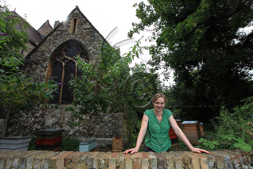 Camilla Goddart, 38 years old, posing in front of her first hive in the garden of St Peters Church in Brocley where she started 8 years ago. Since, this graphic designer by training created a company, &quot;Capital Bee&quot;, that sells honey in the markets or in shops and caf&Egrave;s like Broca Market, Brockley, The Frog on the Green Deli in Nunhead, Cafe Crema in New Cross and El's Kitchen in Ladywell.<br /> &quot;I go through various obsessions, when I was young it was growing tropical fruit, when I was at Cambridge it was English Literature, then art, then japanese woodcuts, then extraordinary victorian copper jellymoulds for puddings at banquets, then herbs and their uses, then decorative vegetable gardens and making potagers, then antique african masks, though in the end keeping bees has proved to be the most enduring as they are so complex and are teaching me all the time about their mysterious world.  I even look after nests of bumblebees now in wooden boxes in the apiary they are terrific characters, people get them mixed up with bees and sometimes want them removed, though it is always best to leave them alone ideally as they rarely do any harm &ordf;