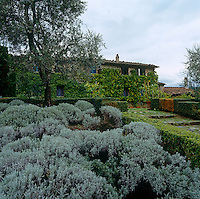 Wide steps lined by box hedges and lavender lead to the entrance of this villa near the village of Montalcino in Tuscany