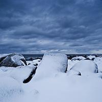 Snow covered rocky coastline near Kvalness, Lofoten islands, Norway