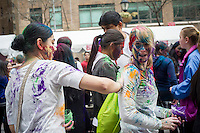 Colored powder is applied to the faces of participants as they celebrate the Indian holiday of Holi at a street festival in Dag Hammarskjold Plaza in New York on Sunday, March 31, 2013.  The spring holiday of Holi, also called Festival of Colors, is celebrated by throwing and wearing colored powder.  (© Frances M. Roberts)