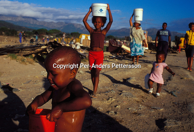dienvfi00088.Environment Fire Strand, South Africa. January 19.  Unidentified children carrying water in buckets from a water tap, a day after a shack fire on January 19, 2004, in a poor township outside Strand, South Africa. Shack fires are very common, as they are built very close to each other and people are using paraffin stoves, which easily fall over, and the fires spread quickly. About 300 shacks were burned to the ground in a couple of hours and about 1500 people were homeless and lost all their possessions. South Africa is facing a severe backlog of housing for the poor. The government has built about 1,7 million houses since 1994, but the backlog is still 6-7 million, still forcing people to live in dangerous shacks in appalling conditions without running water or electricity..©Per-Anders Pettersson/iAfrika P