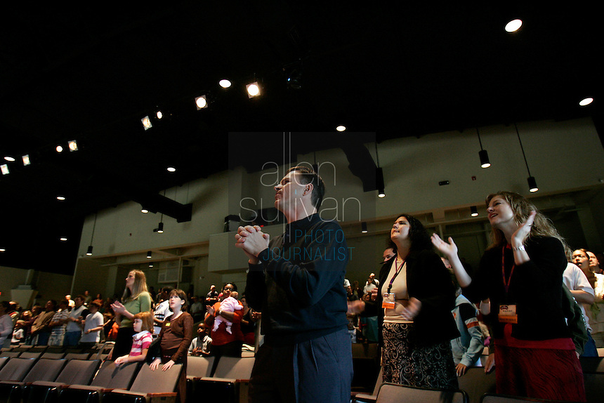 Pastor Marty Baker sings with the congregation at Stevens Creek Church. Baker installed kiosks at the church where people can make donations with credit cards or check cards. So far, he said, up to 25 percent of donations to the church come through the kiosks and he expects about $200,000 from them this year.<br />