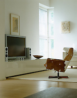 A low-level plasma screen with a custom-made chair upholstered in cow-hide in this contemporary living room