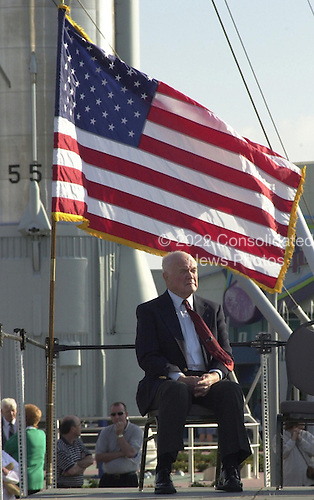 Space pioneer John Glenn Jr. is caught in a moment of reflection under the waving U.S. flag during opening ceremonies for the 40th anniversary celebration of American spaceflight on February 24, 2002. The site is the Rocket Garden in the KSC Visitor Complex at Cape Canaveral, Florida.Credit: NASA via CNP